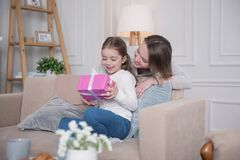 Delighted girl holding her gift. My present. Lovely happy girl holding her gift and her mom standing behind her Royalty Free Stock Photo