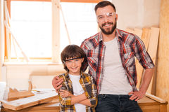 My professional follower. Cheerful young male carpenter embracing his son while standing in workshop Royalty Free Stock Photos