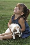 My rabbit. Young girl with pet rabbit in grass Stock Photography