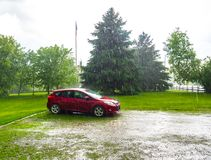 My red car. Heavy rains fell on the ground. This machine was washed by all the falling water. It was quite intense. Drummondville, Quebec, Canada; May 31, 2018 Stock Images