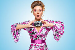 My retro camera. Retro photo of an amazed fashionable hippie homemaker, holding an old vintage photo camera with two hands and showing emotions on blue royalty free stock image