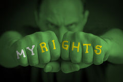MY RIGHTS written on an angry man's fists. MY RIGHTS written on the fingers of an angry man's fists. Green colored. Message concept image Stock Photography