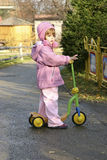 On my scooter. Child riding a scooter on an autumn day Stock Photo