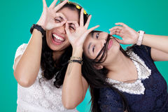 My silly besties. Portrait of two cheerful girls posing to camera expressively, over bright turqoise background Stock Image