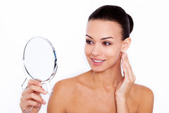 My skin feels great. Shot of a beautiful young woman looking at herself in small mirror over white isolated background Stock Images