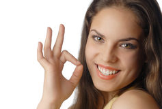 My skin and teeth are OK. Beautiful smiling model with OK gesture with well-conditioned skin and teeth Stock Image