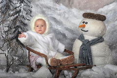 On my sled. Girl on a sled next to a snowman Royalty Free Stock Photos