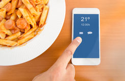 With my smartphone at the lunch. Hand touching the screen of smartphone on the table at the meal time. All screen content is designed by my and not copyrighted Royalty Free Stock Photography
