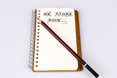 My story book on the white with brown pencil. My story book on the white, Diary with text and pencil Stock Image