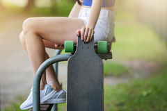 My style, my passion. A photo of girl sitting on the bench in park and holding skateboard Royalty Free Stock Photography