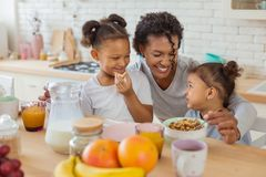 Amazing curly-haired child listening to her mommy. My support. Cute brunette women expressing positivity while embracing her daughters royalty free stock photography