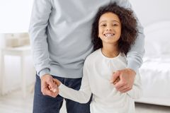 Inspired girl standing near her dad. My supportive dad. Pretty joyful curly-haired girl smiling and standing near her dad and her dad holding her hand Stock Photography