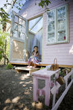 My sweet home. Little girl in her wood house for playtime Stock Photo