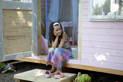My sweet home. Little girl in her wood house for playtime royalty free stock images