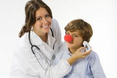 My temperature is ok. Young and cute female doctor measuring temperature to a little boy royalty free stock photography