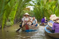 MY THO, VIETNAM - NOVEMBER 24, 2018: Mekong River Delta jungle c. Ruise with unidentified craftman and fisherman rowing boats on flooding muddy lotus field in royalty free stock photography
