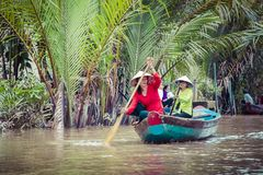 MY THO, VIETNAM - NOVEMBER 24, 2018: Mekong River Delta jungle c. Ruise with unidentified craftman and fisherman rowing boats on flooding muddy lotus field in stock photo