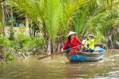 MY THO, VIETNAM - NOVEMBER 24, 2018: Vietnamese women in the traditional Vietnamese cap paddle a small boat with tourists on. The Mekong River in My Tho city in stock image