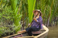 MY THO, VIETNAM - NOVEMBER 24, 2018: Vietnamese women in the traditional Vietnamese cap paddle a small boat with tourists on. The Mekong River in My Tho city in royalty free stock photos