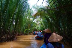 My Tho, Vietnam: Tourist at Mekong River Delta jungle cruise with unidentified craftman and fisherman rowing boats on flooding mud stock photos