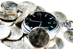 My Time Makes Money. A pocket watch in a pile of quarters. Focused on the second hand on the number 12 Stock Image