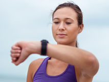My timing is just great. Sporty young woman looking at her wristwatch stock images