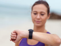 My timing is just great. Sporty young woman looking at her wristwatch royalty free stock images