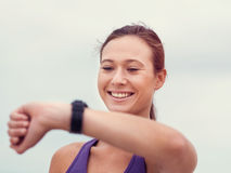 My timing is just great. Sporty young woman looking at her wristwatch royalty free stock photo