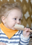 Is that my toothbrush?. 8 month old baby trying to brush his teeth with a hairbrush Stock Images