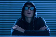 Cool male hacker stealing data. My victory. Tranquil skillful male hacker crossing hands while putting on glasses and hood and posing on the background Royalty Free Stock Images