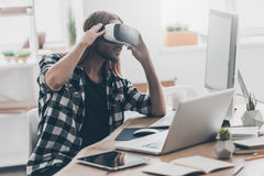 In my virtual world. Handsome young man with long hair adjusting his VR headset while sitting at his desk in creative office Royalty Free Stock Photography