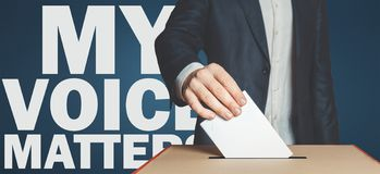 My voice matters concept. Male voter holds hand a ballot above the ballot box stock image