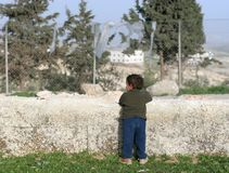 My Wall, Palestine. Young boy leans on a low wall watching for his mother to return home, West bank Israel royalty free stock photos