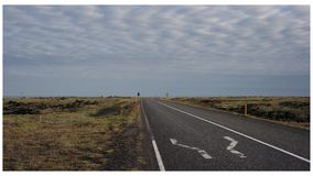 On my way. A road in the middle of nowhere passing lava field in Iceland Royalty Free Stock Photos