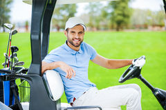 On my way to the next hole. Side view of young happy male golfer driving a golf cart and looking at camera Royalty Free Stock Photography