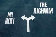My way vs the highway choice concept. Two direction arrows on asphalt Stock Photo