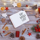 My Wish List text in note pad on christmas flat lay. My Wish List in note pad on christmas flat lay table with image photo frame and light chain shining Royalty Free Stock Photos