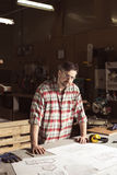 My work is my passion. Carpenter in safety glasses standing beside workbench in workshop Stock Image