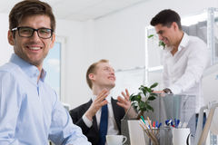 My work is my passion. Happy office worker, in the background two businessmen talking, light interior Stock Photo