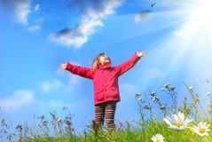 My world. Little girl standing with outstretched arms Stock Photo