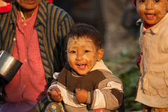 Myanman boy at market. BAGAN, MYANMAR - JANUARY 25: Smile of a child whos sitting on the lap of his mother, who was selling vegetables in the market. People life Royalty Free Stock Photo