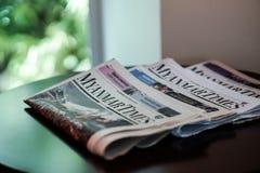 Myanmar cronometra o jornal na tabela em um hotel Fotografia de Stock