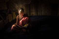 Myanmar - December 5, 2016:Little Novice Monk are reading the book in the cubicle of temple with window light, Mandalay Stock Photography