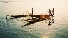 Myanmar, Inle Lake. Fishermen on vintage boats sail home with a catch stock video