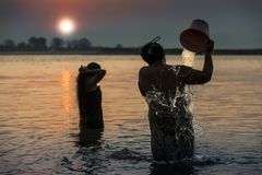 Myanmar - Morgenbad innerhalb Irrawaddy-Flusses stockfoto