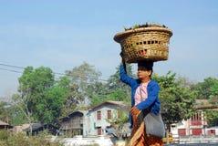Myanmar woman  carrying  basket on her head. Stock Image