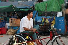 Myanmarese man sitting on his bicycle tricycle taxi for waiting passenger at the market in Yangon royalty free stock photo
