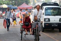 Myanmarese neofita michaelity obsiadanie na rowerowym trójkołowa taxi z kierowca jazdą w alleyway Yangon zdjęcie stock
