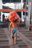 Myanmese-Arbeiter tr?gt gro?e Taschenkokosnu? ausschiffen vom Schiff und vom Weg hinter der Br?cke des Hafens in Rangun-Fluss lizenzfreies stockfoto