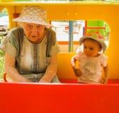 Mycket äldre farmor som talar med hennes lilla sondotter på lekplats, båda bärande hättor, rött tomt bräde royaltyfri fotografi